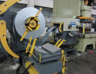 Leveling machine with metal strip material being fed into stamping press